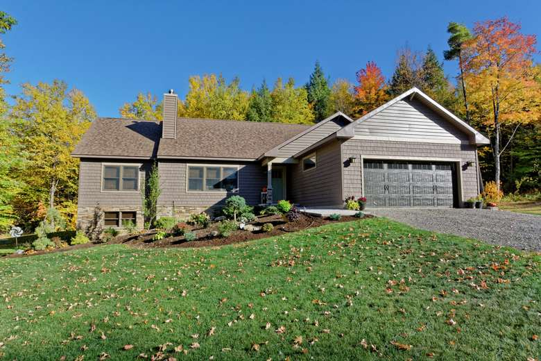A large two story home with attached garage in front, on a sloped lot