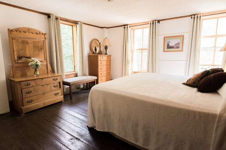 a clean bedroom with a wooden dresser and a bed with white covers