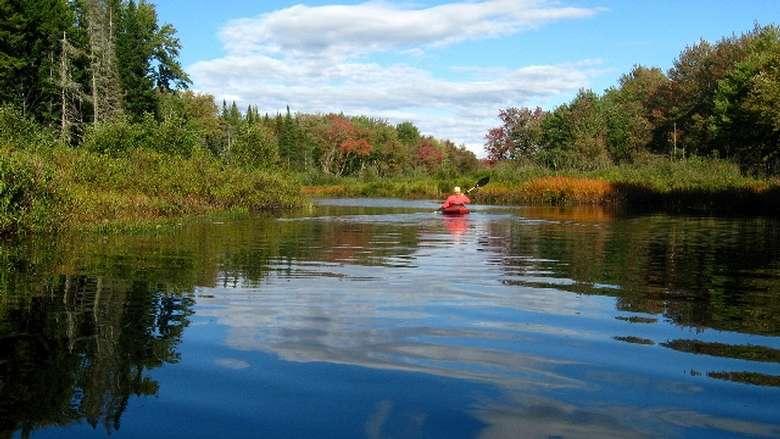 a person paddling along a calm lake