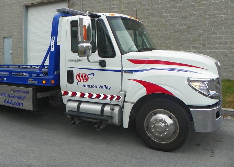 A Triple A tow truck - white with red and blue striping. The triple A logo and the words Hudson Valley are displayed on the side.
