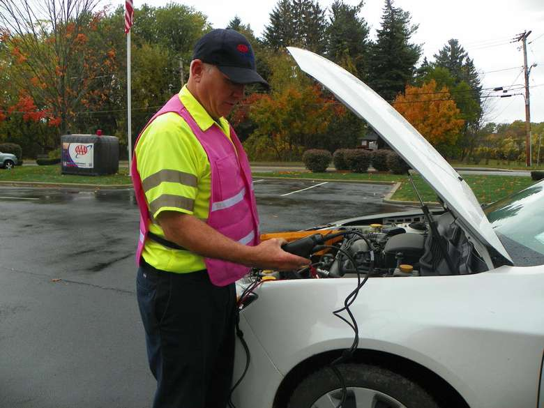 A man wearing a baseball cap with the triple A logo and a bright pink reflective vest, and a bright yellow shirt with reflective stripes on the sleeves, has the hood up on a car, and is looking at an instrument/tool connected to the car.