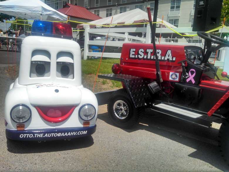 A closeup of the small white model car with sirens on top. The bumper states Otto.The.Auto@AAAHV.com. There is a tractor to the left that has E.S.T.R.A on its side.