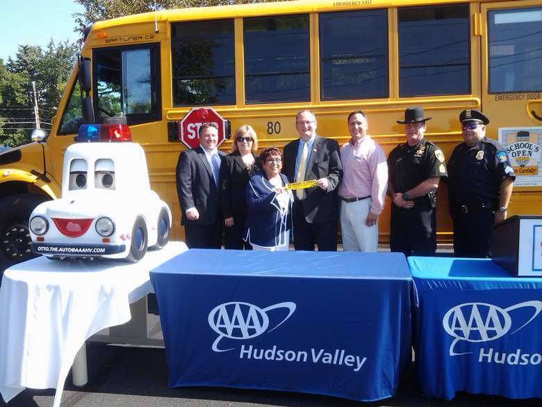 Several people, including two police officers, are standing in front of a bus. There are two blue tables in front of them, and a small white model of a car with sirens on it to the left. A women and a woman are holding up a piece of yellow paper. The text is unreadable.