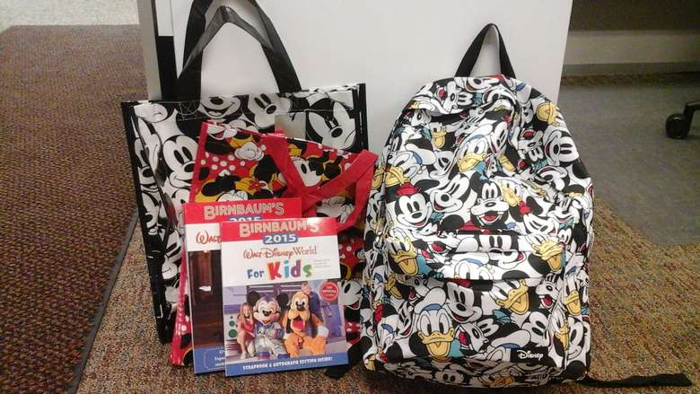 Two Walt Disney Themed Tote Bags and a Walt Disney Themed Backpack. In front of the tote bags are two books. The book in front states Birnbaum's 2015 Walt Disney World for Kids. There is an image of Mickie Mouse, Pluto and a child on the front.