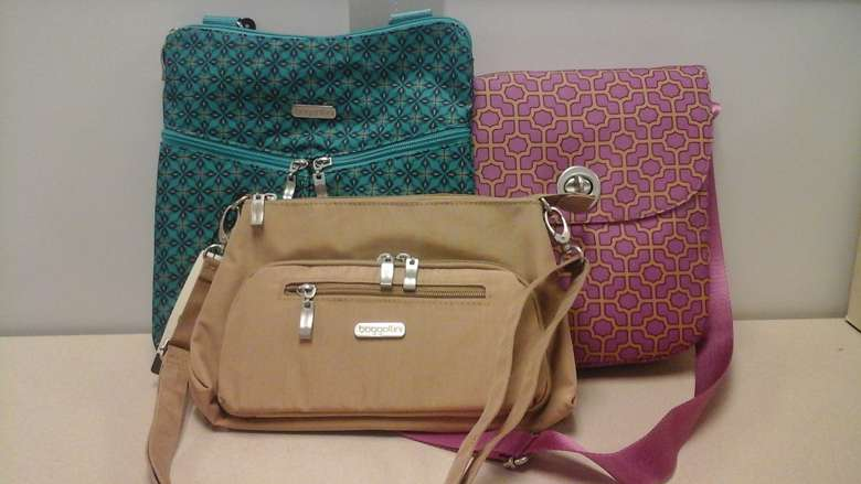 Three Baggallini cross-body purses, one is tan, one is green and the other is pink.
