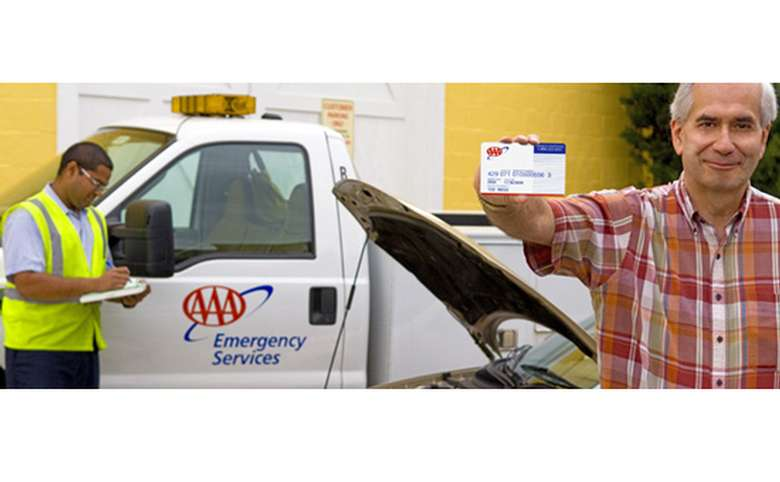 A man is holding out his triple A membership card and smiling. Behind him is a truck with the triple A logo and the words Emergency Services on the side. A man in a yellow reflective vest is writing notes on a pad.