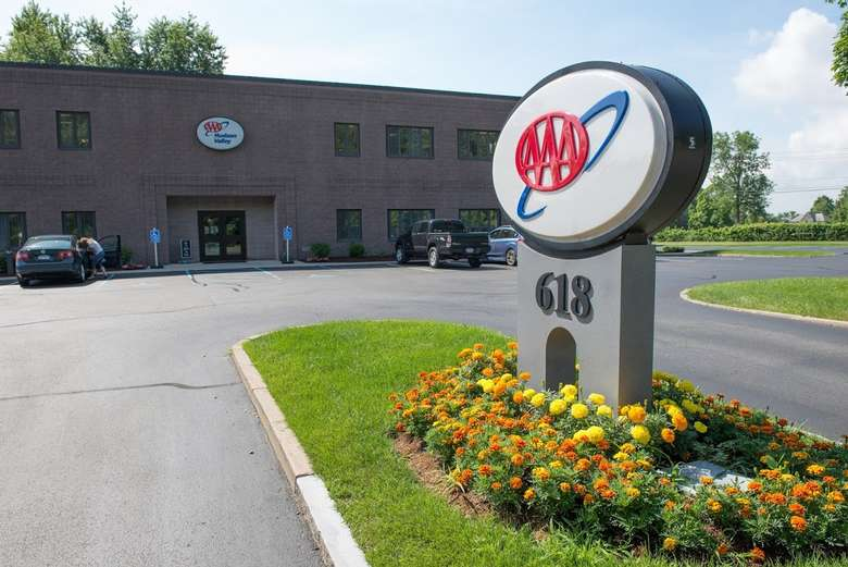 The exterior of the triple A Hudson Valley office. There are two handicapped parking spots on each side of the entrance. Yellow and orange flowers are planted around a triple A sign that displays the logo and the number 618