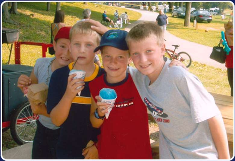 four boys, three of whom are eating sno cones