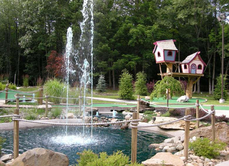 mini-golf course with a water feature in the middle and whimsical looking treehouses in the background
