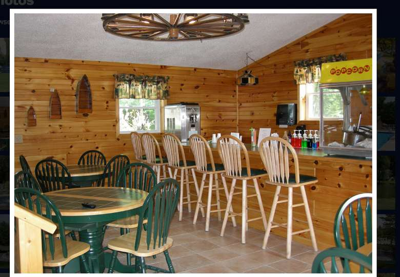 concession or bar area in a log room with bar stools and lower tables and chairs