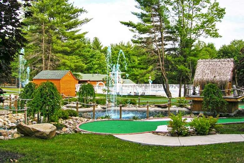 mini golf course with water features spouting up into the air