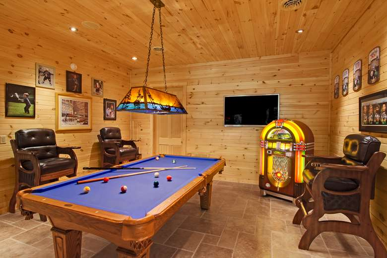 pool table in a room with pine walls and a pine ceiling