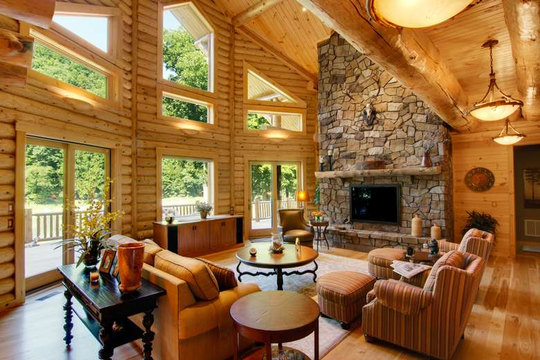 great room in a newly constructed log home with a tall stone fireplace