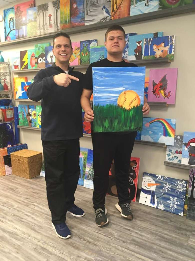 man standing next to kid with painting