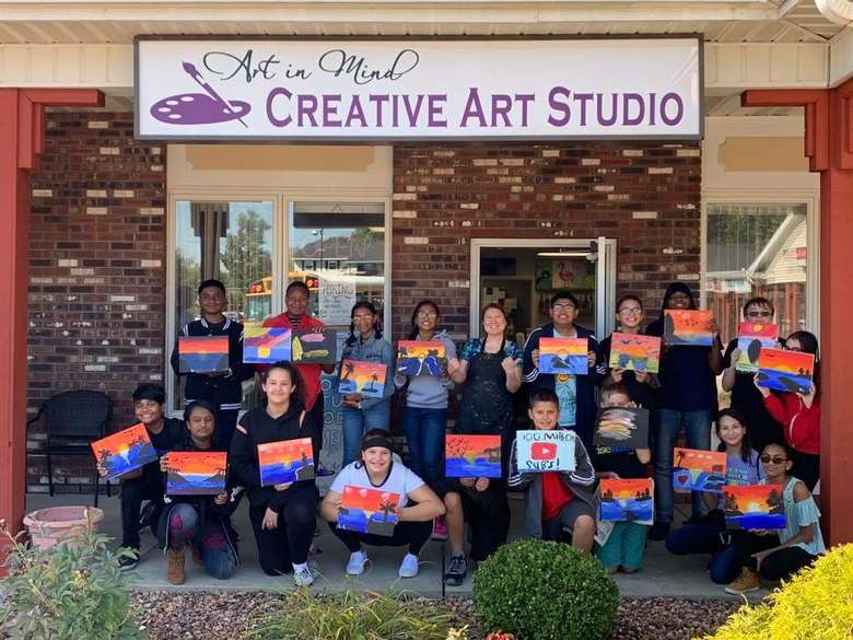 kids holding up painted signs in front of studio with sign