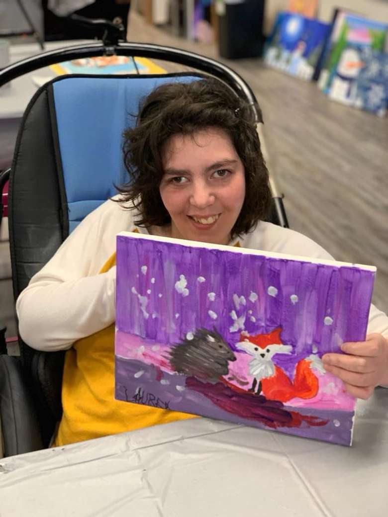 woman in wheelchair holding up painting