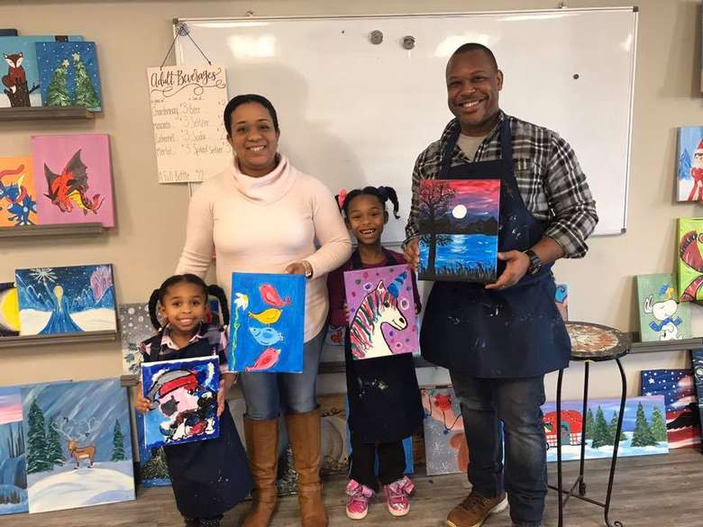family holding up paintings they painted
