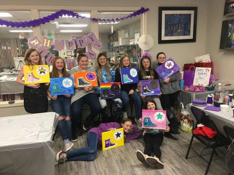 kids from birthday party posing with paintings