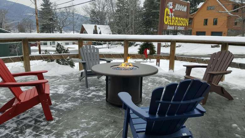 adirondack chairs around a fire pit in winter