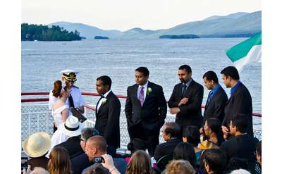 boat captain marrying a bride and groom as the guests look on