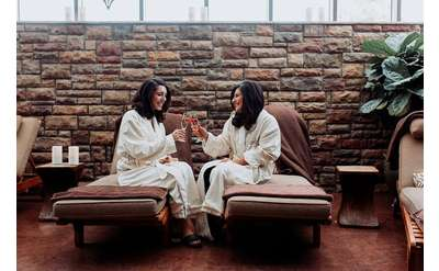 two women wearing spa robes and holding drinks