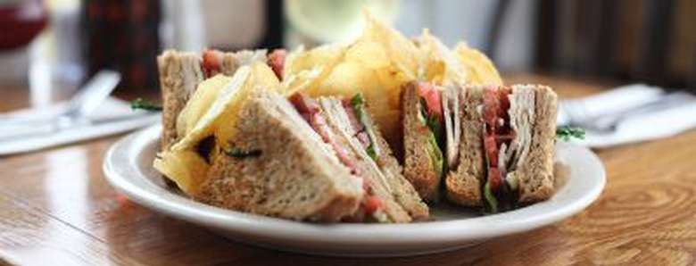 three layers of turkey club sandwich cut into four pieces and served with potato chips
