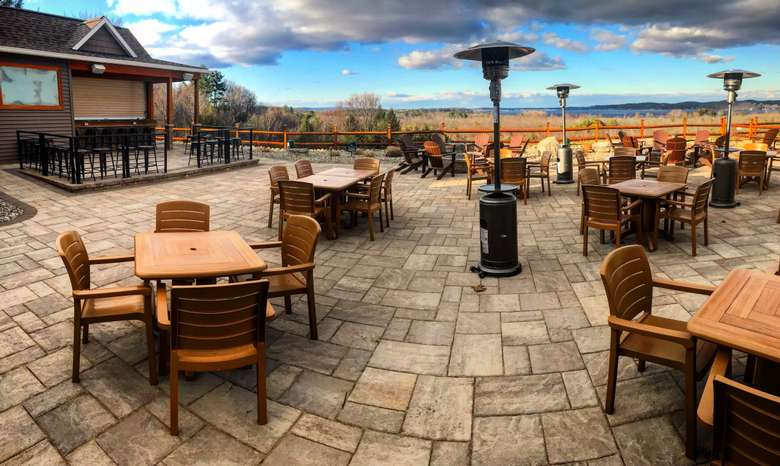 another view of the outdoor overlook patio with several tables and heat lamps