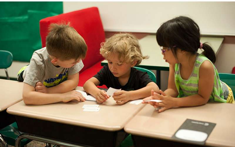 three kids sitting at desks with small pieces of paper