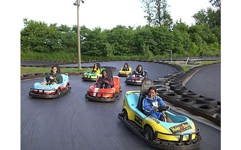 six people in go-karts driving around a track