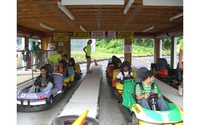 people seated in go-karts getting ready to take off onto the course