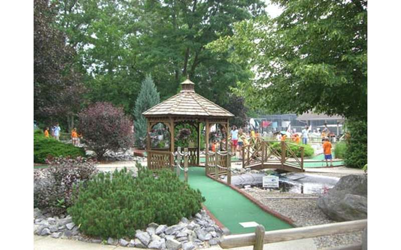 a brown gazebo over part of a mini-golf course