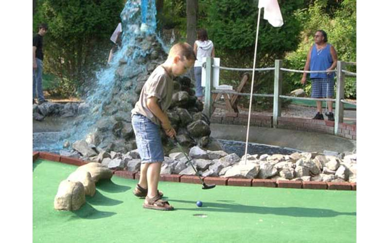 a young boy holding a golf club on a mini-golf course