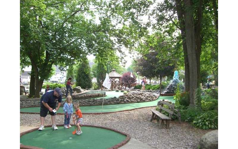 a man with two kids on a mini-golf course