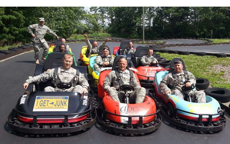 men dressed in camo military uniforms in go-karts