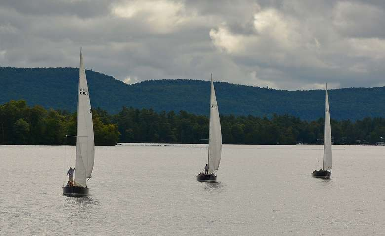 three sailboats in a row in the water