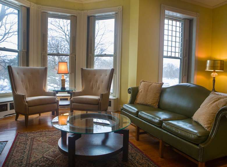 leather couch and two chairs in front of a bay window