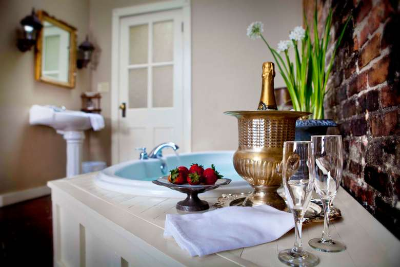 bottle of champagne, two glasses, and a tray of strawberries next to a soaker tub