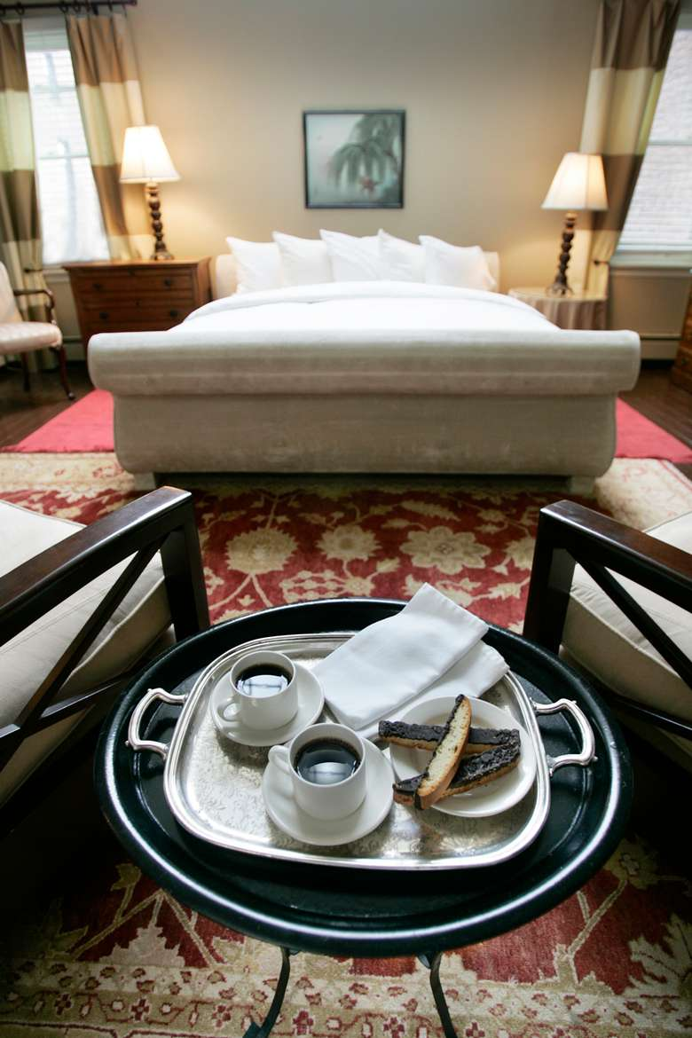 silver tray with two cups of coffee and a plate of biscotti with a king size bed in the background