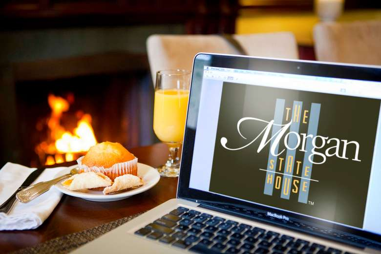 laptop computer with the morgan state house's website pulled up on a table with a pastry and orange juice in front of a fireplace
