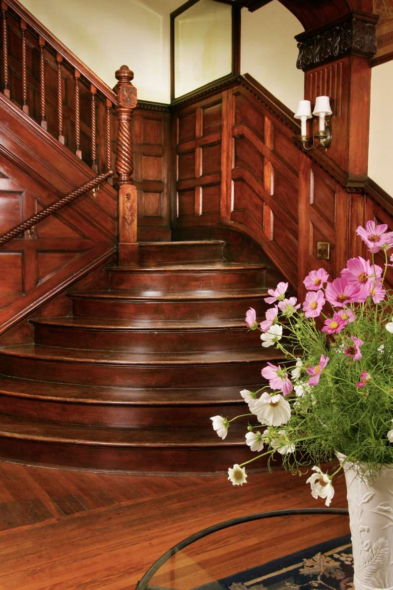 large wooden staircase with flowers on a table in front of it