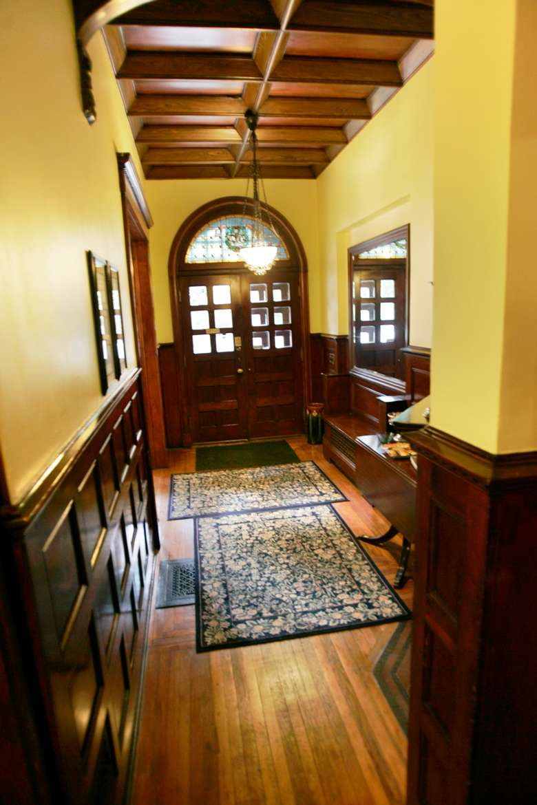 yellow hallway with wood accents and a large wooden and glass door at the end