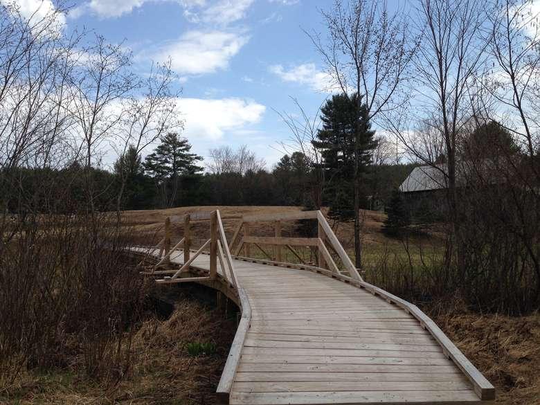 handicap-accessible wooden bridge crossing a creek