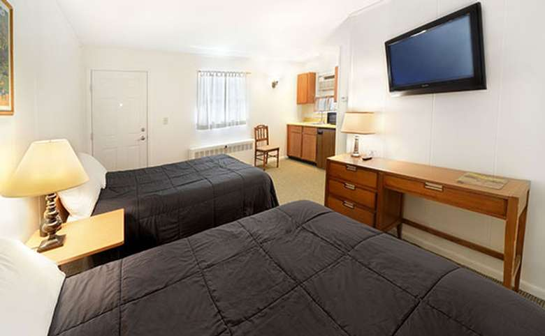 motel room with two double beds and a flat screen tv mounted to the wall