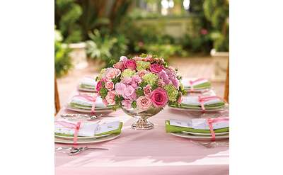 pink and red flowers arranged on a wedding reception table