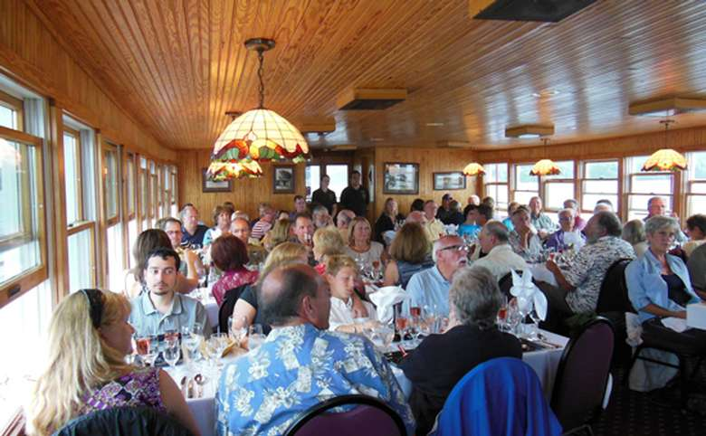 dozens of people sitting at tables inside a steamboat