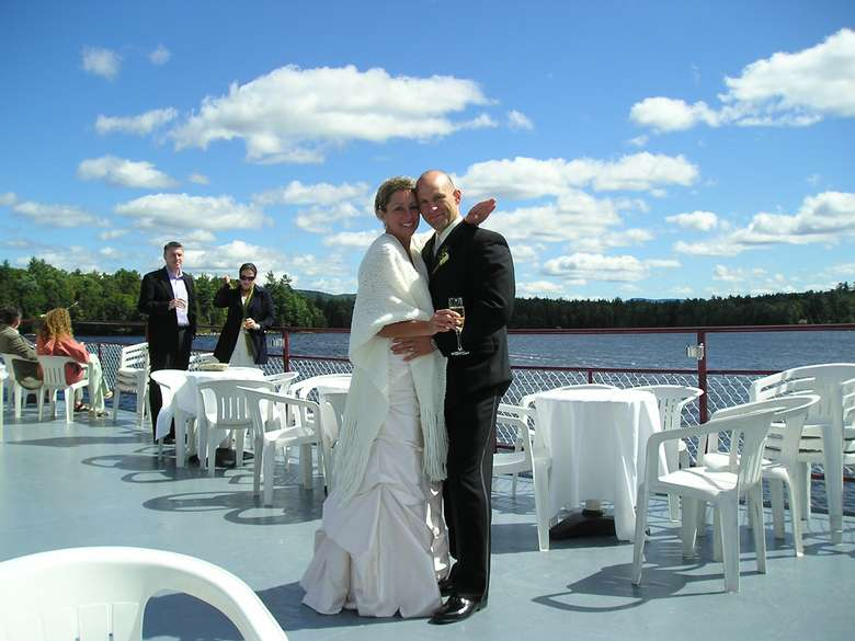 bride and groom posing on a steamboat deck