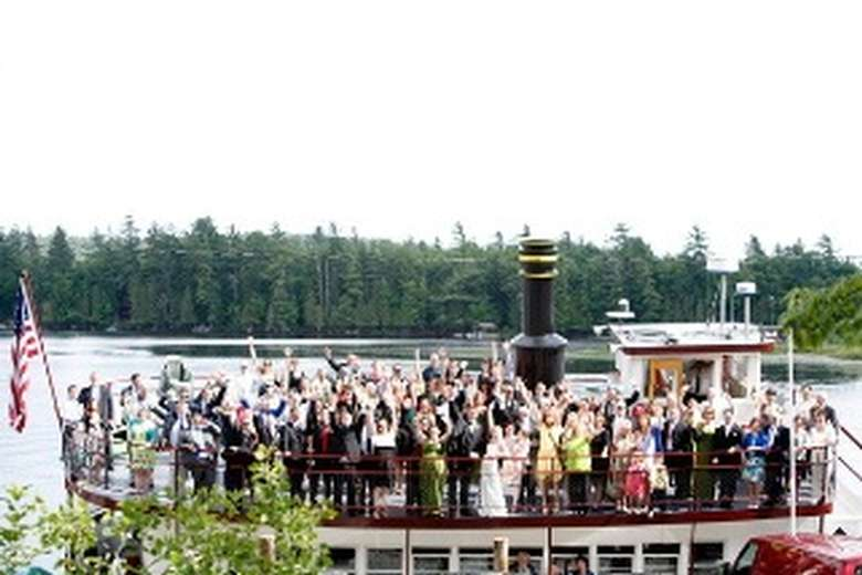 wedding guests waving from the upper deck of a steamboat