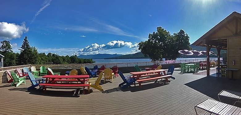 colorful picnic tables and chairs overlooking lake george on a sunny day