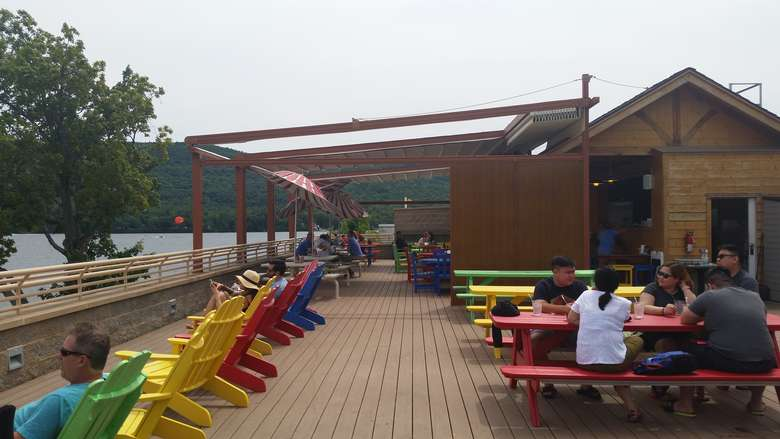 people sitting at colorful picnic tables on a rooftop deck with other colorful chairs overlooking lake george