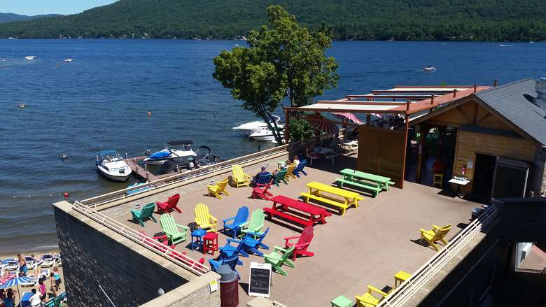 aerial view of a rooftop deck with colorful chairs and tables overlooking lake george